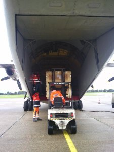 A few small CubeSats in a large case being loaded into a special cargo hold